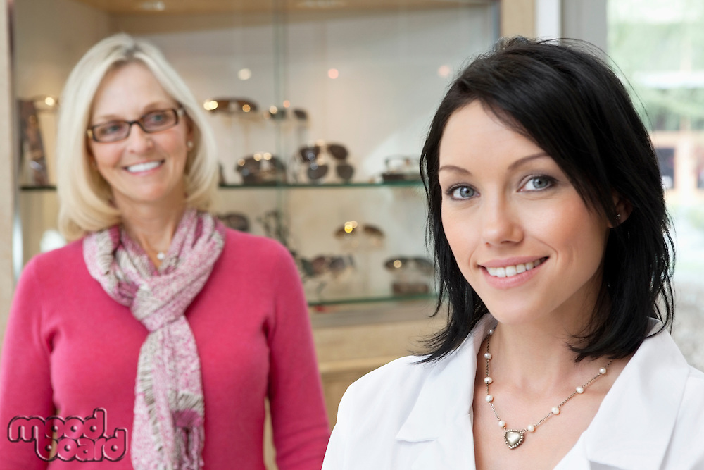 Portrait of a mid adult optician with happy female customer in store