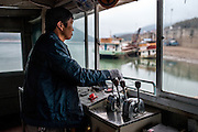 The captain of a sand dredging vessel mans the cockpit in the early morning in the town of Simaogangzhen, Yunan, China.  The dredged sand is sold locally and to large scale construction sites in nearby major cities such as Kunming and Jinhong.