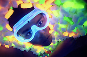 Young man with glowing safety goggles in a pile of glowing packing peanuts.Black light