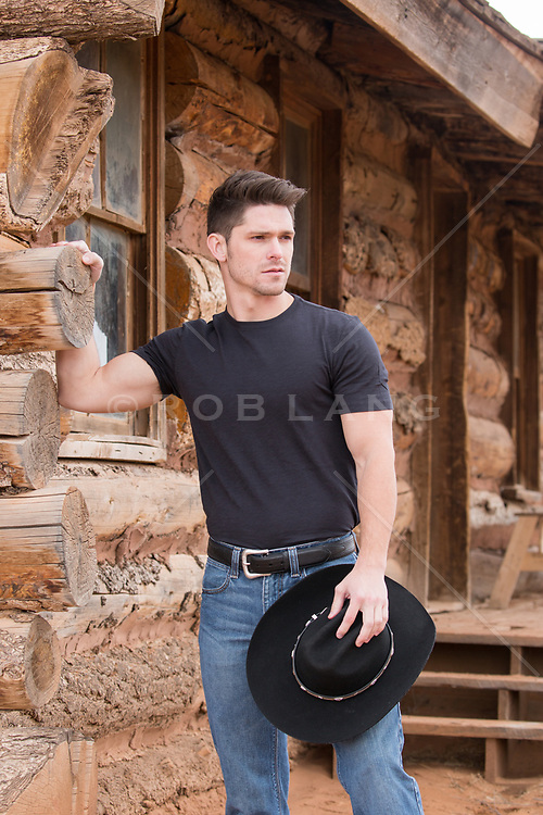 hot All American cowboy by a rustic cabin