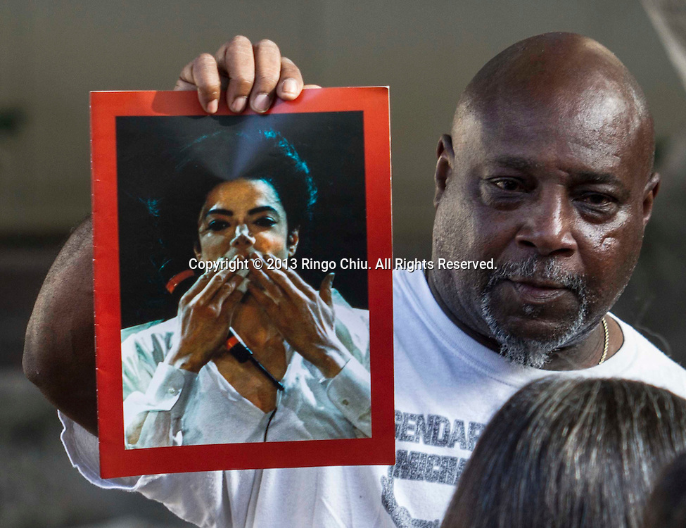 Vincent Woods, a Michael Jackson fan holds up a portrait of Jackson as jury foreman Greg Barden talks to reporters outside a courthouse on Wednesday, Oct. 2, 2013, in Los Angeles. A jury cleared AEG Live of negligence in a case that attempted to link the death of Michael Jackson to the company that promoted his ill-fated comeback shows. (Photo by Ringo Chiu/PHOTOFORMULA.com)