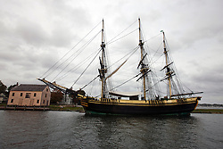Friendship of Salem docked next to a boarded up saltbox style building, Salem Maritime National Historic Site, Salem, Massachusetts, United States of America