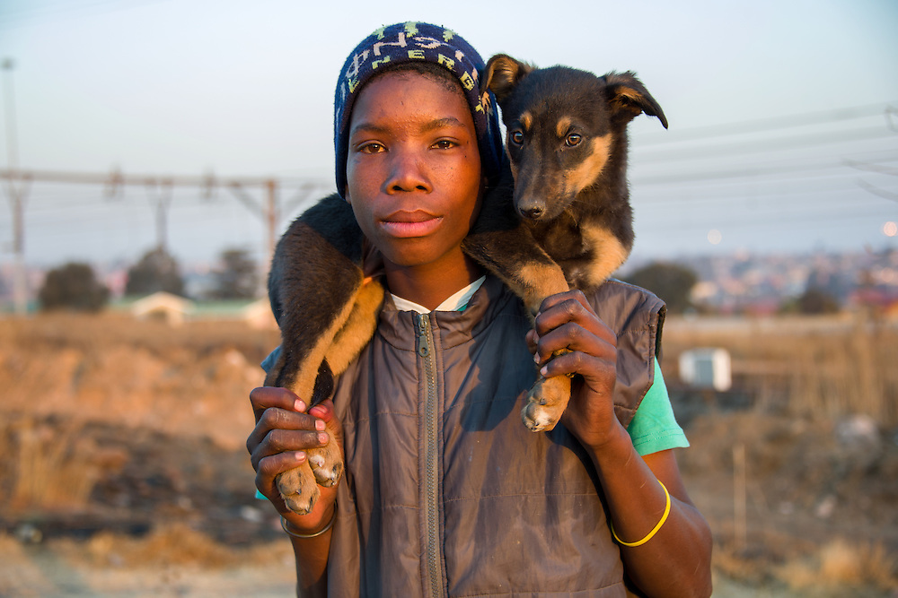 A young boy in Soweto carries his young puppy across the train tracks on their way home.