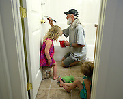 PRICE CHAMBERS / NEWS&amp;GUIDE<br /> Mike Melf puts some finishing touches on the family's bathroom as the girls play in their new home.