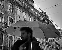Rainy day discussion out on the street under an Umbrella in Lisbon. Image taken with a Leica CL camera and 23 mm f/2 lens.