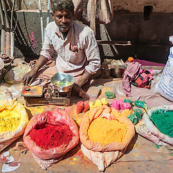 Man selling colors in the streets for celebration of Holi festival. India