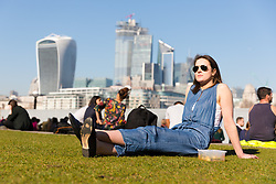 © Licensed to London News Pictures. 26/02/2019. London, UK.  A woman with a lunchbox relaxes in the sunshine in front of City of London skyscrapers on the south bank at lunchtime during another day of unseasonably warm sunny weather in the capital. Photo credit: Vickie Flores/LNP