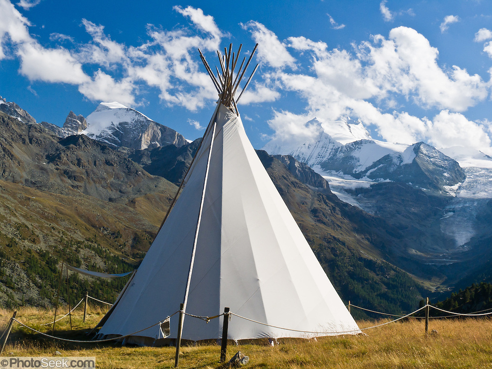 "The sharp peak of Weisshorn (""White Peak"") rises to 4506 meters or 14,783 feet elevation above a tepee (tipi or teepee) tent in the Pennine Alps, Switzerland, on the High Route (Chamonix-Zermatt Haute Route), Europe."