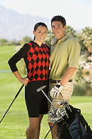 Couple of golfers standing together on golf course (portrait)