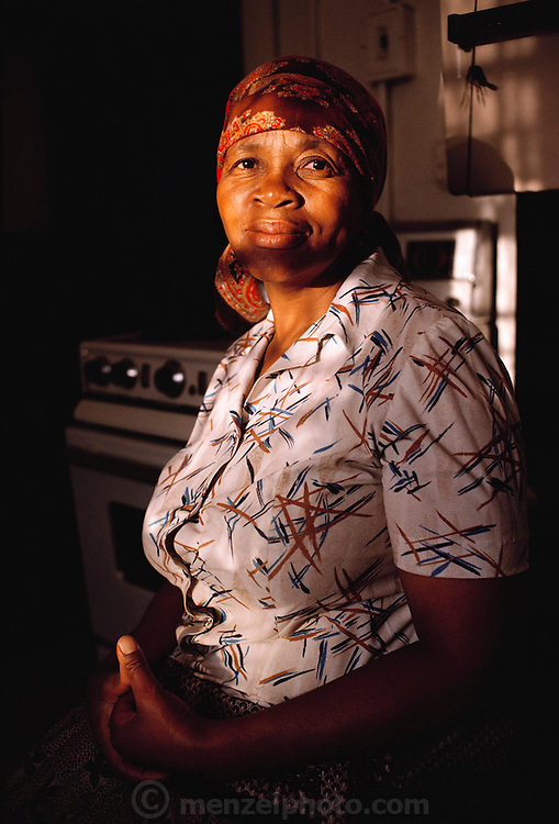 Portrait of Poppy Qampie's mother Leah Nosizwe, 64 in the kitchen of their Soweto home. She sleeps in the second small bedroom with the children.  The Qampie family lives in a 400 square foot concrete block duplex house in the sprawling area of Southwest Township (called Soweto), outside Johannesburg (Joberg), South Africa. Material World Project.