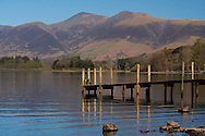 A jetty at Ashness Landing on Derwent Water and the Skiddaw mountain range in the background.  Lake District National Park, Cumbria, UK