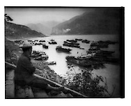 Resting porter surveys moored river boats, Fengjie, Three Gorges River, China.  1997