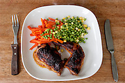 "Sunday dinner of baked chicken, potatoes, and frozen veggies prepared by Jill McTighe at her home in Willesden, London, United Kingdom.  (From the book What I Eat: Around the World in 80 Diets.) The caloric value of her day's worth of food on a ""bingeing"" day in the month of September was 12300 kcals. The calorie total is not a daily caloric average.  Jill is 31 years old; 5 feet, 5 inches tall;  and 230 pounds. Honest about her food addiction replacing a drug habit, Jill joked about being a chocoholic as she enthusiastically downed a piece of chocolate cake at the end of the photo session. Her weight has yo-yoed over the years and at the time of the picture she was near her heaviest; walking her children to school every day was the sole reason she didn't weigh more. She says this photo experience was a catalyst for beginning a healthier diet for herself and her family. ""Do I cook? Yes, but not cakes. I roast. Nothing ever, ever is fat-fried!"" [Use of Jill McTighe images must be used contextually only and use cleared with Peter Menzel Photography on a case by case basis.]"