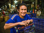 08 JANUARY 2013 - BANGKOK, THAILAND:   A porter waits for customers in the Bangkok Flower Market. The Bangkok Flower Market (Pak Klong Talad) is the biggest wholesale and retail fresh flower market in Bangkok. It is also one of the largest fresh fruit and produce markets in the city. The market is located in the old part of the city, south of Wat Po (Temple of the Reclining Buddha) and the Grand Palace.    PHOTO BY JACK KURTZ