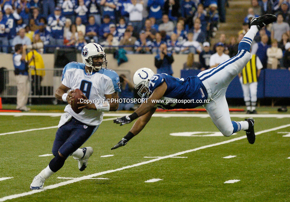 Tennessee Titans quarterback Steve McNair (L) avoids a high diving Indianapolis Colts' Raheem Brock (R) at the RCA Dome in Indianapolis, Indiana, December 4, 2005. Colts won 35-3. Photo: Icon SMI/PHOTOSPORT<br />