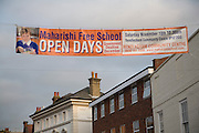 Advertising banner crossing a street for Maharishi Free School planned for Rendlesham, Suffolk, England as part of the government's policy to encourage people to set up state funded small schools. 2012 Woodbridge, England.
