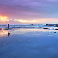 Dramatic sunset in Cornwall, England with distant female teenage figure