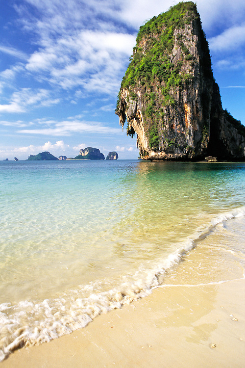 Krabi, Thailand. Waves wash on white sand beach with limestone cliffs beyond.