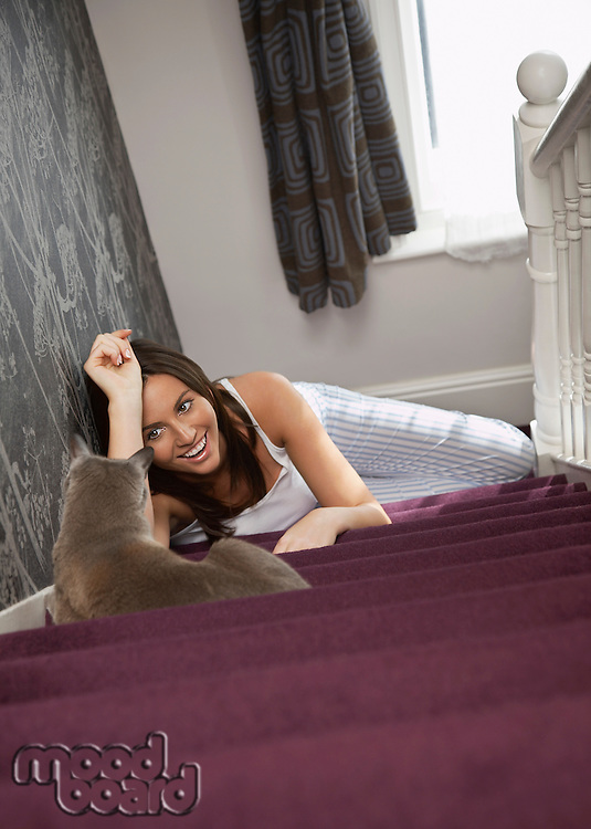 Young woman lying on stairs looking at cat