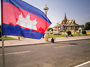 02 FEBRUARY 2013 - PHNOM PENH, CAMBODIA:  A Cambodian flag in Phnom Penh flies at half mast to honor late King Norodom Sihanouk during the mourning period for Sihanouk, who ruled Cambodia from independence in 1953 until he was overthrown by a military coup in 1970. Sihanouk died in Beijing, China, in October 2012. The Royal Palace in Phnom Penh is in the background.      PHOTO BY JACK KURTZ