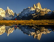 Trekker reflected in pond under Cerro Torre, (left) & FitzRoy, Los Glaciares National Park, Patagonia, Argentina