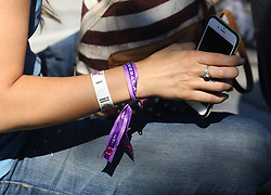 Oct 2, 2017 - Las Vegas, Nevada, U.S. - A women wears Route 91 Harvest entry bracelets and sits outside a barricade near the event area on the Las Vegas Strip. A mass shooting occurred late Sunday evening at the music festival. (Credit Image: © Ronda Churchill via ZUMA Wire)