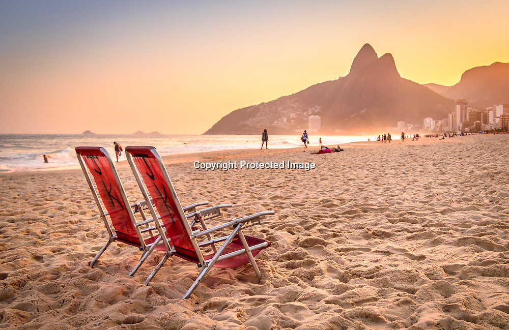 A beach deck chair overlooking the beautiful Ipanema Beach at sunset