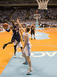 Virginia's Sean Singletary (44) passes the ball mid-air around UNC's Tyler Hansbrough (50).  The #1 ranked Tar Heels beat the Cavaliers 79-69 to improved to 15-1 overall, 2-0 ACC on January 10, 2007 at the Dean Smith Center in Chapel Hill, NC...<br />