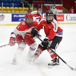 WHITBY, - Dec 15, 2015 -  WJAC Game 6- Team Russia vs Team Switzerland at the 2015 World Junior A Challenge at the Iroquois Park Recreation Complex, ON. Nikita Gromov #4 of Team Russia battles for control with Kaj Suter #7 of Team Switzerland during the second period.<br /> (Photo: Andy Corneau / OJHL Images)