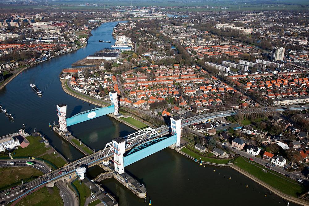 Nederland, Zuid-Holland, Capelle aan den IJssel, 20-03-2009; stormvloedkering in de Hollandsche IJssel. Bij storm en dreigend hoog water wordt een van de twee schuiven naar beneden gelaten, de tweede schuif dient al reserve. De scheepvaart kan de gesloten kering paseren via de naastgelegen schutsluis. Rechts van de rivier Krimpen aan den IJssel.   .De stormvloedkering maakt deel uit van de Deltawerken en is als eerste voltooid in 1958. Ten tijde van De Ramp - watersnood 1953 - werd het zeewater door de storm opgestuwd en dreigde de verzwakte rivierdijken in het achterland het te begeven waardoor grote van het laag gelegen westen van Nederland ondergelopen zouden zijn..Netherlands, Capelle at the river IJssel, near Rotterdam: storm surge barrier, protects the highly populated western part of Holland, which lies below sea level. In case of storm and threat of high water, one of the two doors is lowered into the river (the second door is a spare one). The lock next to the barrier allows shipping when the barrier is closed.Swart collectie, luchtfoto (toeslag); Swart Collection, aerial photo (additional fee required).foto Siebe Swart / photo Siebe Swart