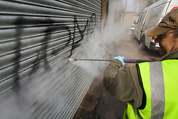 Council worker pressure jetting graffiti off wall and metal shutters Havering London UK