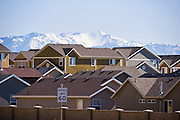 Rows of rooftops in a newly developed subdivision with Utah mountains in the distance.