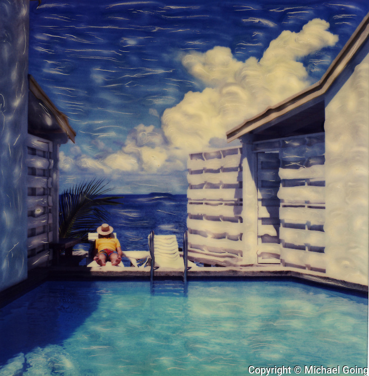 Altered Polaroid photo of swimming pool in foreground, man on lounge chair and ocean with blue sky and clouds