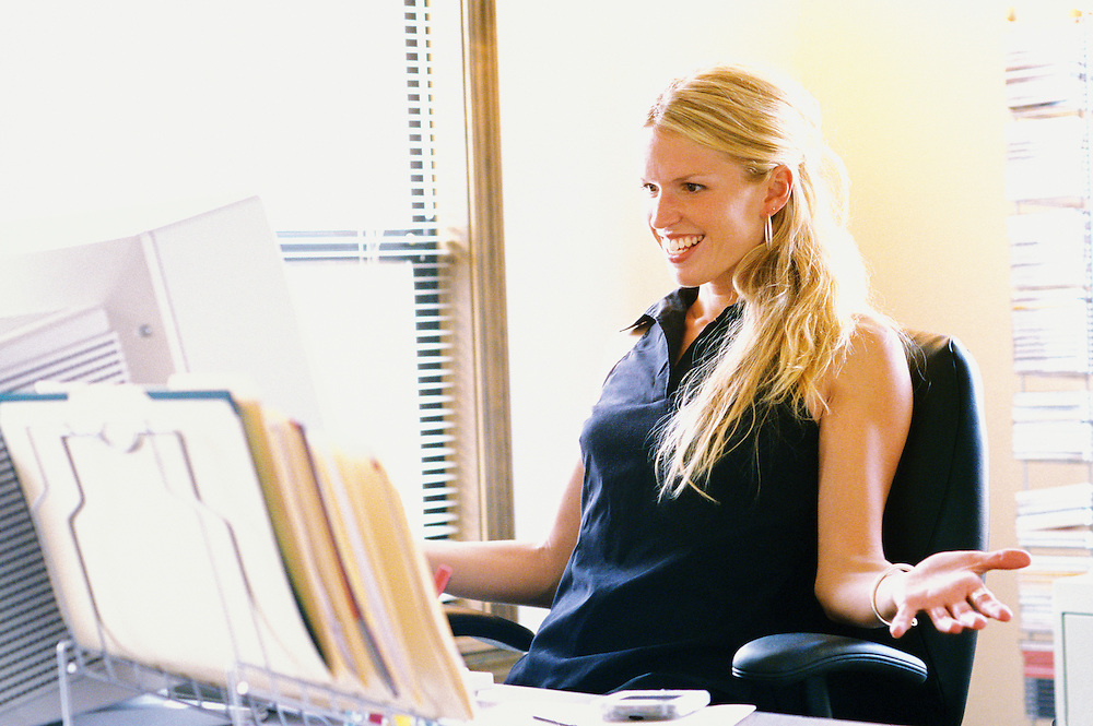 A young woman smiling at her computer as if pleased.