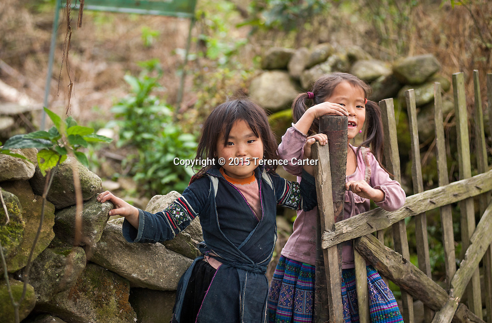 Hilltribe girls play outside their house in the terraced rice fields above Sapa, Vietnam.