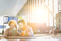 Couple using digital tablet while waiting for their flight in airport with lens flare