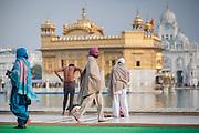 Sikh pilgrims walking around the Golden Temple in Amritsar (India)
