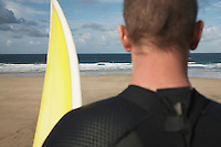 Man holding surfboard on beach looking at sea back view close up