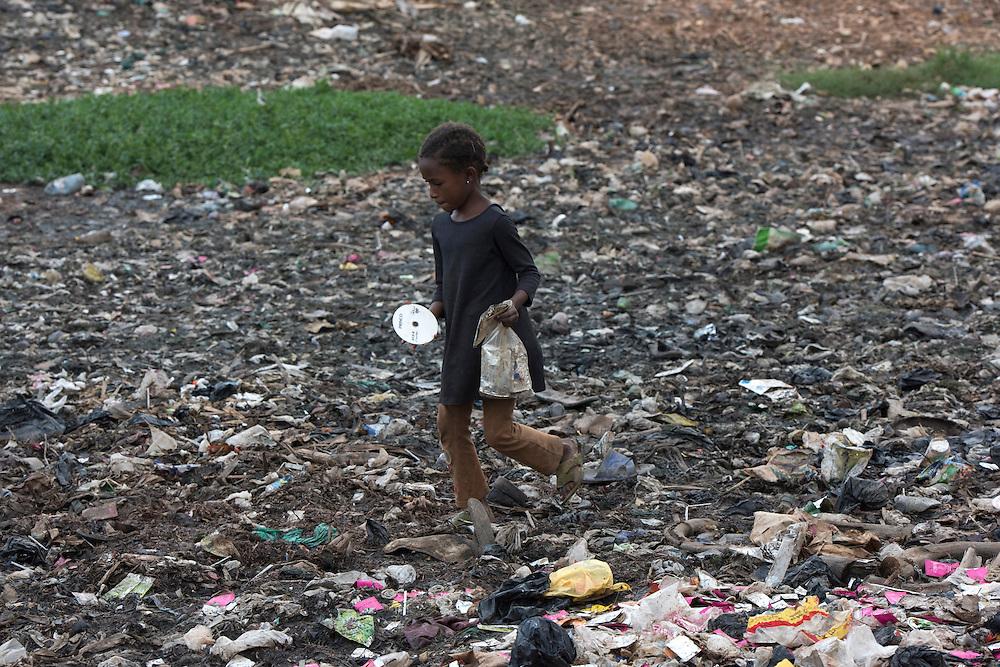 A Congolese girl searching the garbage dump in the Katwe slum in Kampala, Uganda.