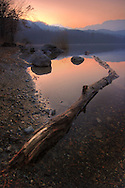 Taken on an evening of mid February at Avigliana Lake, a small lovely lake at the feet of the Alps. I went there just to have a walk around the lake. My intention was just to explore the lake for some new good spot, and then return back at a later date as the light was really flat in the afternoon, due to a deep haze all around. However, just some minute after sunset that haze produced a beautiful glow in the sky, tinging it with stunning oranges and yellows.