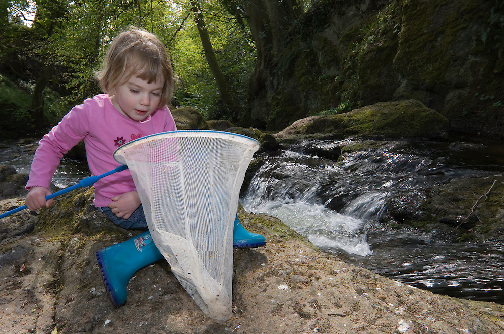 Young girl with net beside a waterfall, Angus, Scotland
