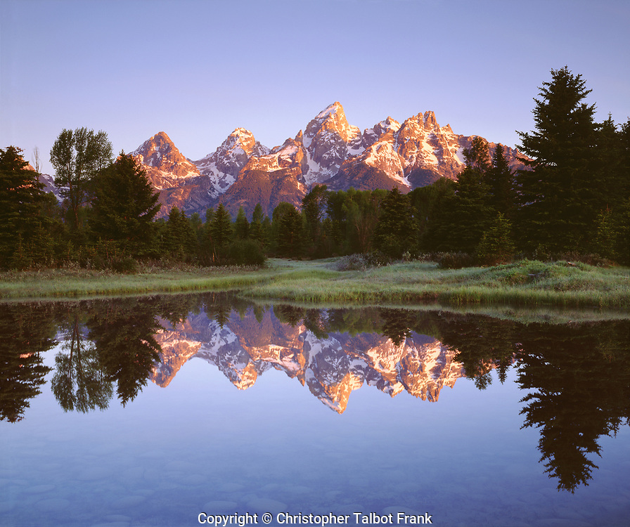 For this very special location along the Snake River, I set up my 4x5 view camera to photograph this Grand Teton mirror image.  My high resolution photo shows the alpine glow lighting up the mountain range which reflects perfectly in the still water.