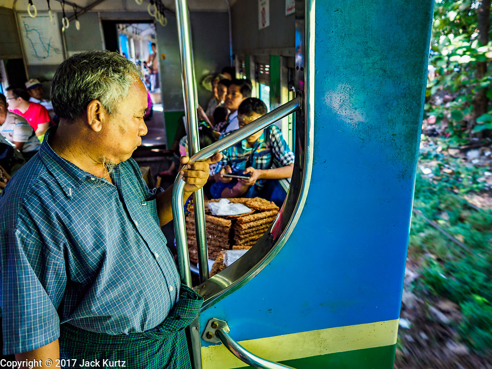 25 NOVEMBER 2017 - YANGON, MYANMAR:  Passengers stand in the doorway of the Yangon Circular Train. The Yangon Circular Train is a 45.9-kilometre (28.5 mi) 39-station two track loop system connects satellite towns and suburban areas to downtown. The train was built during the British colonial period, the second track was built in 1954. Trains currently run both directions (clockwise and counter-clockwise) around the city. The trains are the least expensive way to get across Yangon and they are very popular with Yangon's working class. About 100,000 people ride the train every day. A a ticket costs 200 Kyat (about .17¢ US) for the entire 28.5 mile loop.   PHOTO BY JACK KURTZ