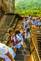 School girls climbing a staircase to the top of Sigiriya Rock (an ancient rock fortress), Central Province, Sri Lanka.