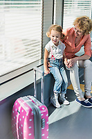 Portrait of mature woman with her cute little daughter looking through the window in airport