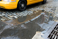 A reflection of a taxi cab in a rain puddle on a New York street in the SoHo district