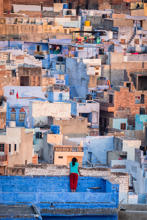 In the rooftop balcony of her home, a girl looks at the maze of houses that is Jodhpur