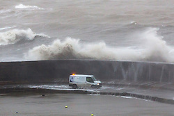 © Licensed to London News Pictures. 27/01/2016. Lyme Regis, UK. A white van gets covered in seawater as  large waves crash over the Cobb at Lyme Regis harbour in  Dorset, south west England at high tide. The tail end of storm Jonas continues to hit the UK, bringing torrential rain and gales. Photo credit: Peter Macdiarmid/LNP