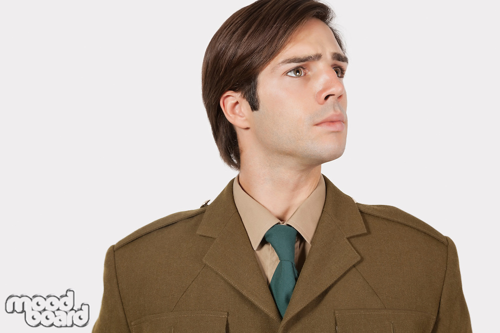Young man in military uniform looking away against gray background