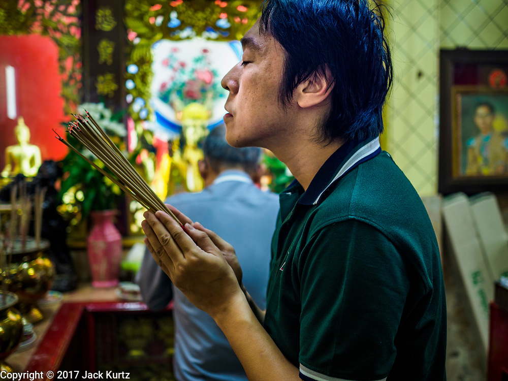 """22 AUGUST 2017 - BANGKOK, THAILAND: A man prays on the first day of Hungry Ghost Month in a small shrine in Bangkok's Chinatown. The seventh lunar month (August - September) is when many Chinese believe Hell's gate will open to allow spirits to roam freely in the human world. Many households and temples hold prayer ceremonies throughout the month-long Hungry Ghost Festival (Phor Thor) to appease the spirits. During the festival, believers will also worship the Tai Su Yeah (King of Hades) in the form of paper effigies which will be """"sent back"""" to hell after the effigies are burnt.      PHOTO BY JACK KURTZ"""